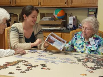 Emilia Varrone '16 building a puzzle with Kendal residents