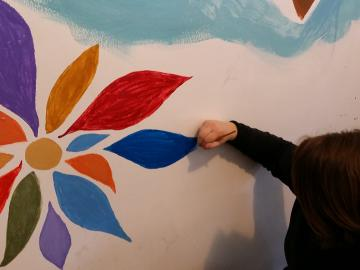 Student painting a flower on a wall