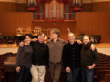 Five people standing in front of the stage in Warner Concert Hall; Elizabeth Ogonek, Stephen Hartke, Xak Bjerken, Timothy Weiss, and Jesse Jones