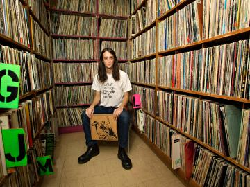 Adrian Rew '13 surrounded by shelves full of LP records