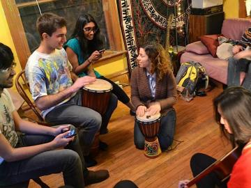 Group of people seated in a circle playing music with an acoustic guitar and djembe drums.