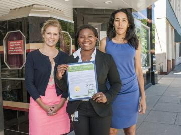 Serena Hendricks outside of the Apollo Theatre holds a certificate of commendation presented by a representative from the office of Secretary of State John Husted