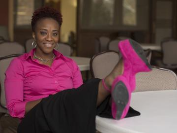 Armina Patton sits wearing a pink shirt and black pants, with her feet up
