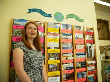 Picture of woman standing next to wall of brochures