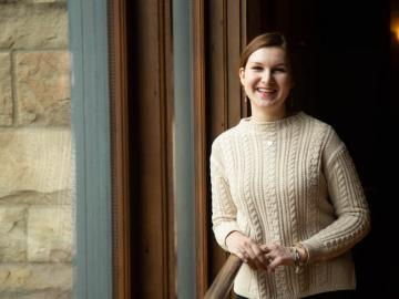 Picture of woman in beige sweater standing by a window.