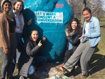 Five students in front of a blue painted rock