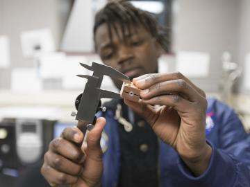 Close-up photo of Daniel Mukasa working with tools in the lab