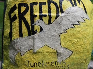 "A rock painted with a dove and the words ""Freedom Juneteenth 2013"""