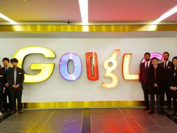 Groups of students stand before an electric Google sign