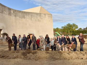 Individuals use shovels during a groundbreaking ceremony for the The Eric Baker Nord Performing Arts Annex and Hall Annex.