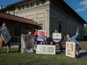 students on lawn holding art work