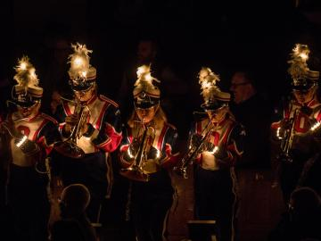 A marching band performs with lights in their hats.