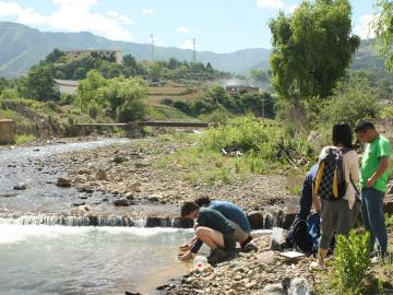 Students taking soil samples from the edge of a river