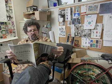 Man with glasses sitting in chair office, reading a magazine, next to a bicycle
