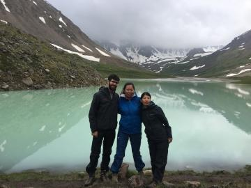 Three people standing in front of mountains and lake. Photo.