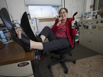 Jill Medina sits at her desk wearing scuba flippers
