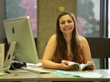 Julia Berrebi holding a book and smiling, sitting at a desk in the Writing Center