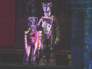 two puppets standing next to each other on stage