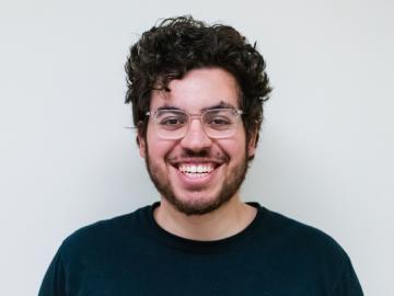 A smiling  León Pescador wearing darak t-shirt.