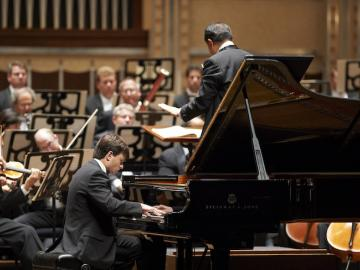 Pianist performs with orchestra.
