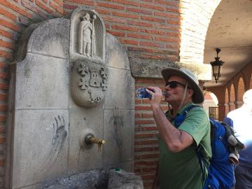Michael Reynolds drinking water from a bottle in front of a water fountain