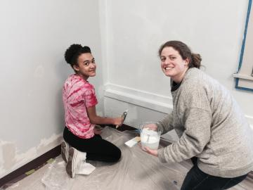 A girl and a young woman paint a baseboard together.