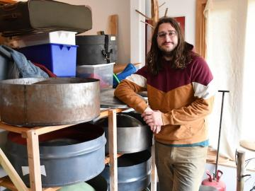 Noah Sanderson leaning against racks filled with steel pan. Photo.