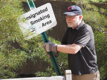A man holds a metal post with a sign reading 'Designated Smoking Area'