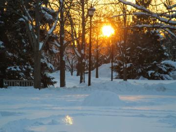 sun setting on winter snow scene.