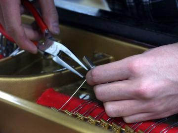 A technician works on a piano.