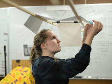 A student inspects a sheet of paper that is draped over 2 wooden rods above her..