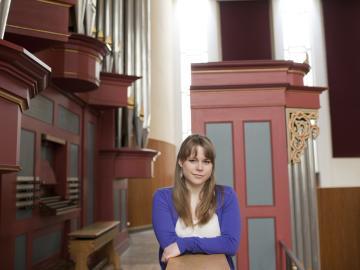 Katelyn Emerson '15 posing next to an organ loft