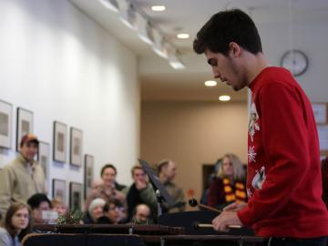 A student in a winter holiday sweater plays the marimba