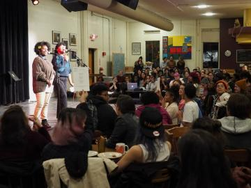 Two poets speak to an audience at the Cat in the Cream