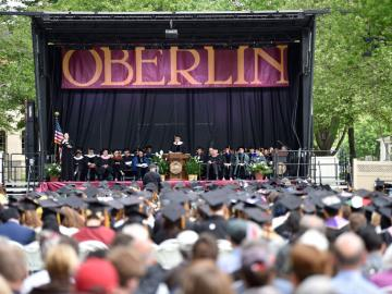 A view of the Commencement speakers on stage under an 'Oberlin' banner. The audience in the foreground is a sea of graduation caps.