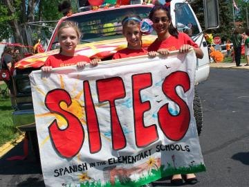 3 school-age girls hold a sign that reads SITES Spanish in the Elementary Schools