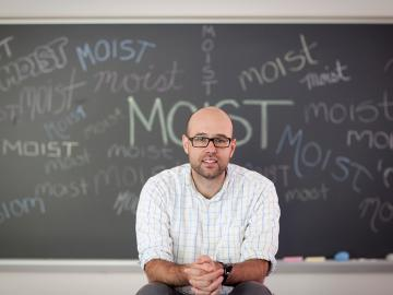 Man seated in front of chalkboard showing the word 'moist'