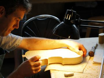 Under a bright lamp, a man works on unfinished wood in the shape of a violin body