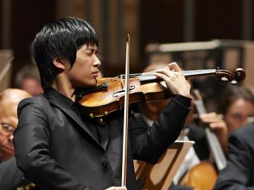 Young violinist performs with orchestra