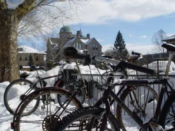 Bicycles on a bike rack, surrounded by snow.