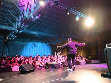 A rapper performs in front of a large crowd of excited students.