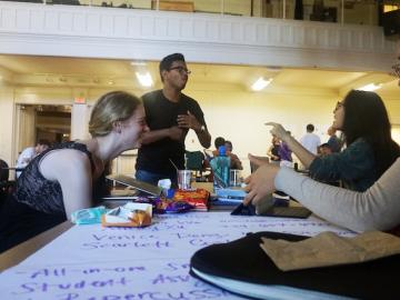 Students talking at a table.