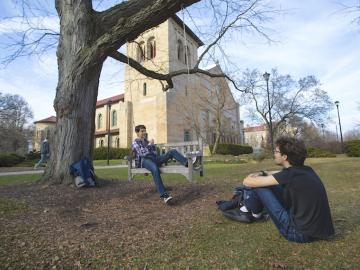 One student sits on the grass and another student sits on a swing.