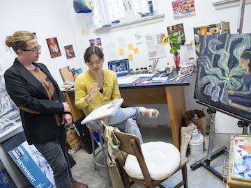 art teacher discussing painting with a student.