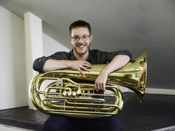 male student sitting with a tuba and smiling.