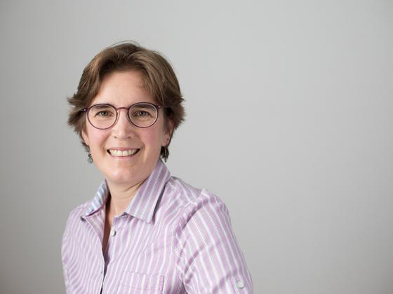 woman seated wearing glasses and wearing purple striped blouse.