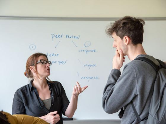 """Janet Fiskio motions with her hands, speaking to a student, against a whiteboard that reads """"peer review"""""""