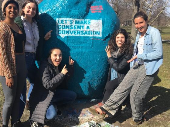 Five students in front of blue painted rock