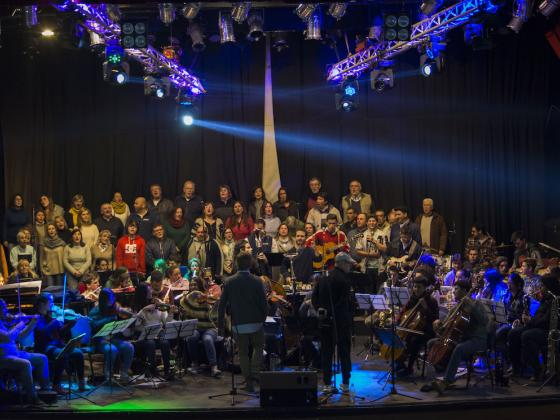 Orquesta Participativa large group of singers and musicians on stage.