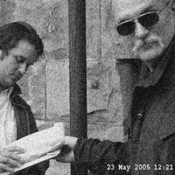 A mysterious man in sunglasses grabs a notebook held by another.